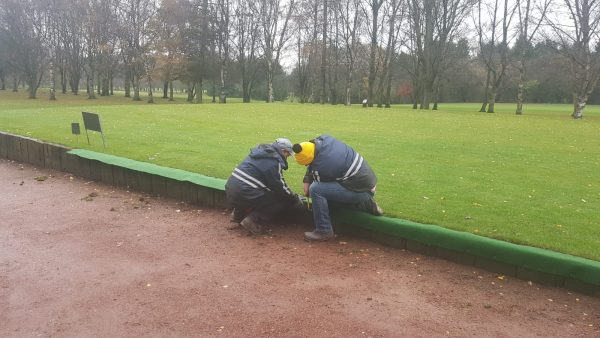 Neil and Sam fitting matting to 1st tee